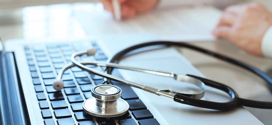 doctor working near keyboard and stethoscope